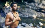 Shirtless man sitting beside river meditating with hands over heart.
