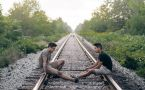 Two men sitting on railroad tracks talking