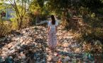 Woman standing in a road covered in plastic and home garbage