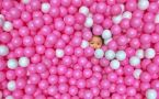Young child's face pokes out of pink and white balls