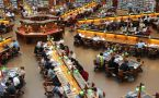 View from above of a university library with many students at study tables.