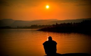 Sunset silhouette of a person alone at the edge of a lake.