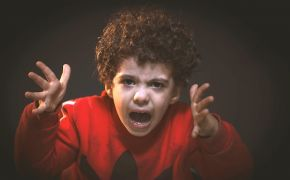 Child in red shirt yelling in anger.