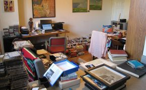 very cluttered apartment with piles of belongings