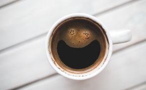the bubbles in a coffee cup make the shape of a smile