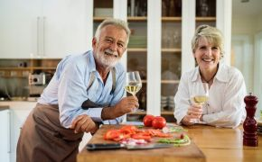 Couple in the kitchen preparing food with wine
