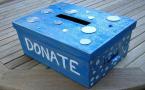 """blue homemade charity contribution box with """"DONATE"""" printed on side"""
