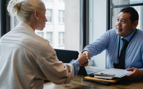 A man and woman shake hands across a desk at work.