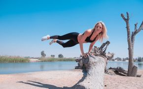Woman in workout clothes jumping over fallen tree.