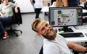 Smiling man at desk at work wit note on his forehead - BE HAPPY