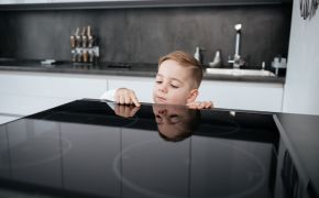 A child peers over kitchen counter to touch surface of stove