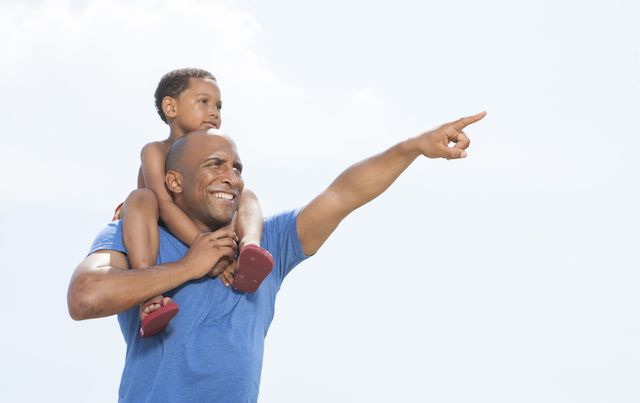 Father with boy on his shoulders, pointing off into distance.