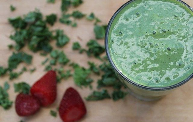 Top view of green smoothie in glass with strawberries on table.