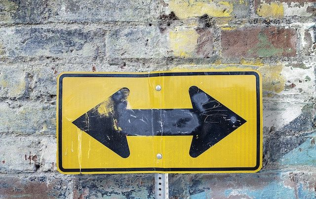 Yellow traffic sign with black arrows pointing opposite directions