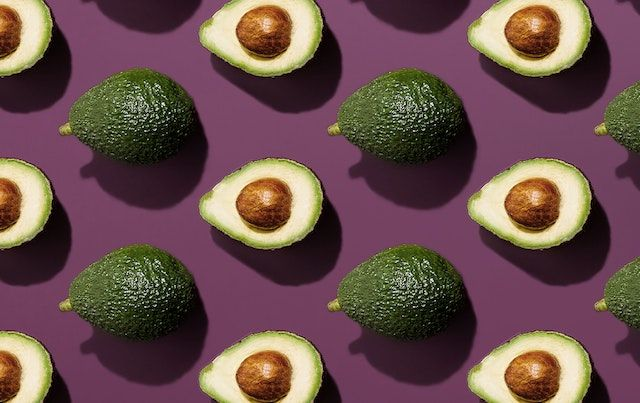Whole and half avocados arranged on a purple table.