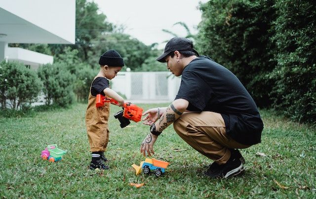 Father and son playing with toys in back yard.