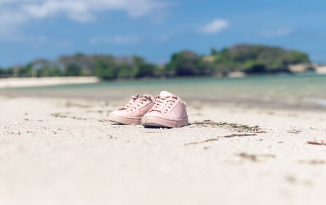 Pair of pink sneakers on a long beach.