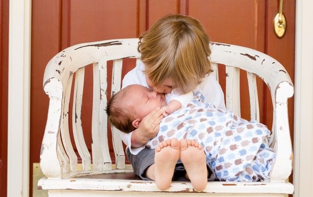 a young boy cuddles his baby brother in a white chair