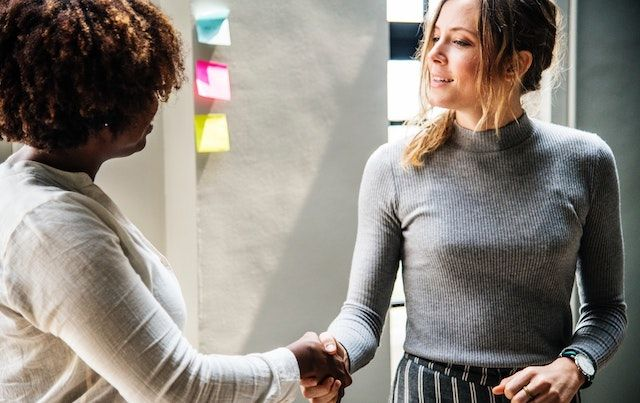 Two women shaking hands over business deal.