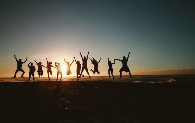 Silhouette image of several people jumping for joy on beach at dusk.