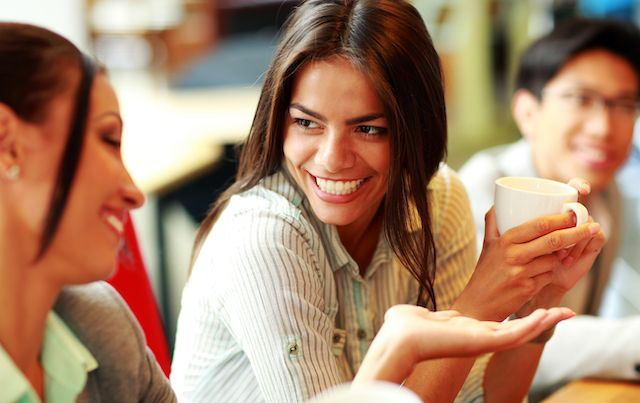 Woman laughing with friends while drinking coffee