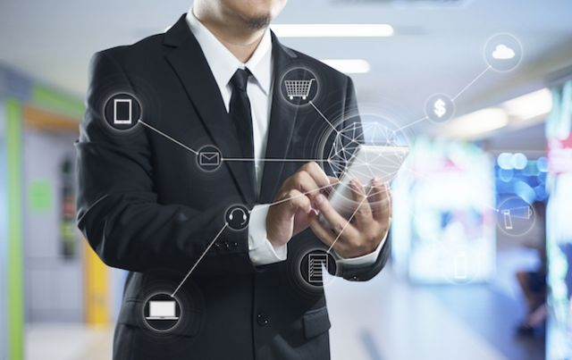 Businessman using connected app with symbols on mobile phone