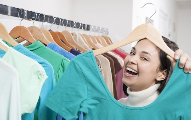 Woman standing in front of rack of clothes holding up shirt on hanger