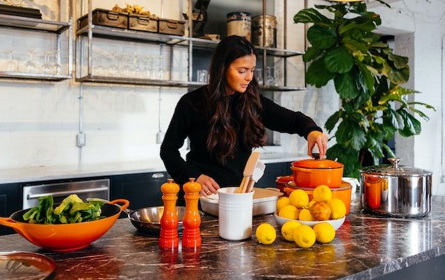 Woman in kitchen using orange pots and pans to cook healthy food.