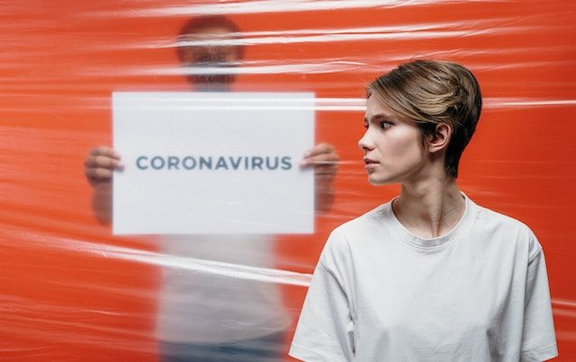 Woman in front of a plastic sheet, behind is a man with sign says CORONAVIRUS