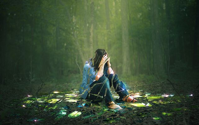 A woman, head in hands, sits depressed on the forest floor