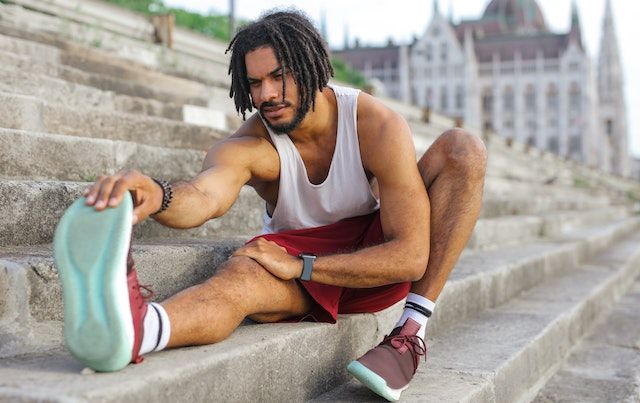 Man stretching for a run on concrete steps