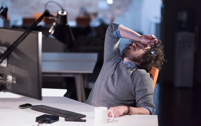 Exhausted man sleeping at his desk.
