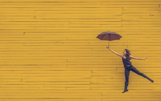 Woman dressed in black flying in air with umbrella in front of yellow wood wall.
