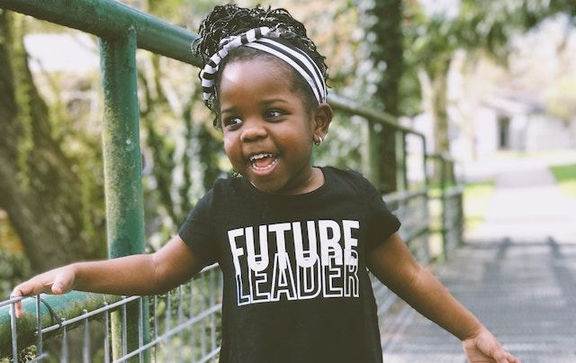 Young girl laughing wearing shirt that says FUTURE LEADER