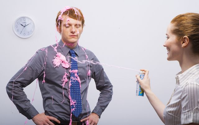 Laughing woman sprays unamused man with Silly String