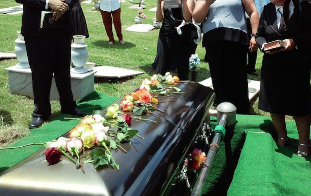 Mourners gather around a casket graveside.