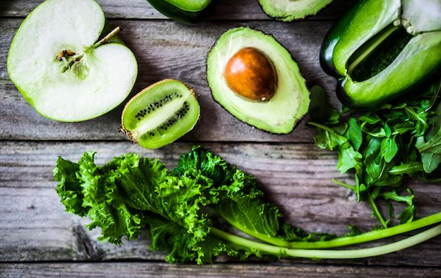 Assortment of green fruits and vegetables on wooden table.