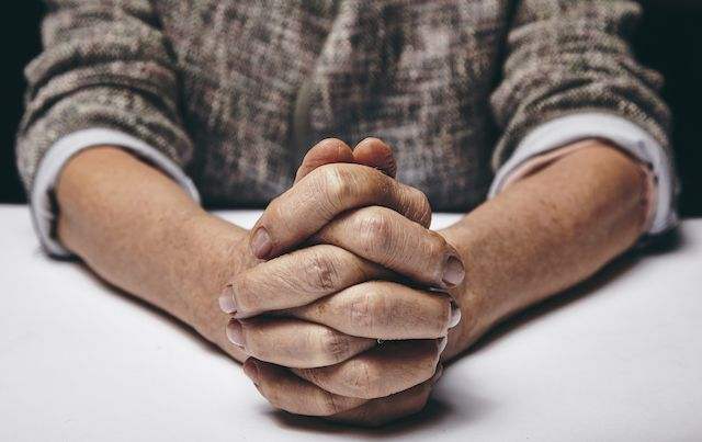 Person with hands folded together on white table