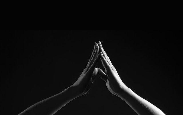 Black and white shot of two hands gently touching fingertips