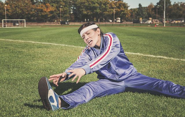 woman in track suit stretching with effort