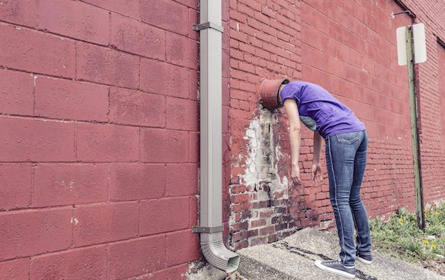 Woman leaning against red wall helplessly with head in a pipe