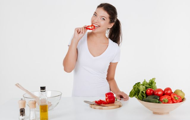 Young woman cooking with vegetables while eating them.
