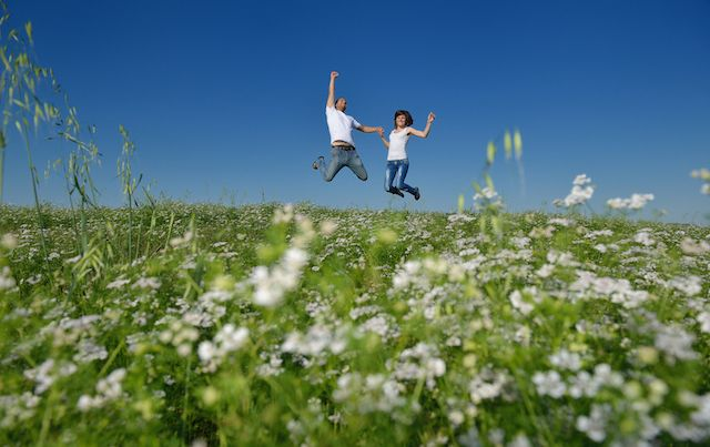 Couple on a flowered hill jumping into the air.