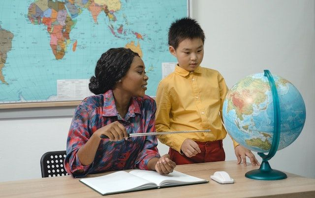 A teacher pointing to globe helping student learn.