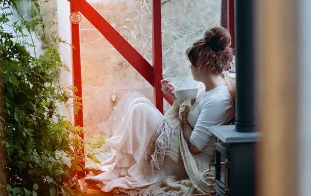 Woman sitting up in bed with bowl of cereal, looking out the window