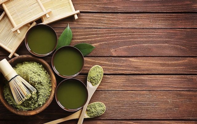Green matcha powdered and prepared tea and cups on wooden table