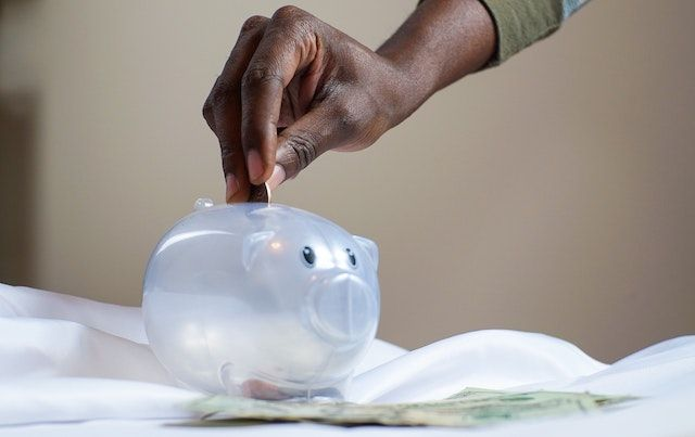 Hand dropping coin into piggy bank