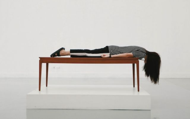 Woman laying, exhausted, on table top in white room