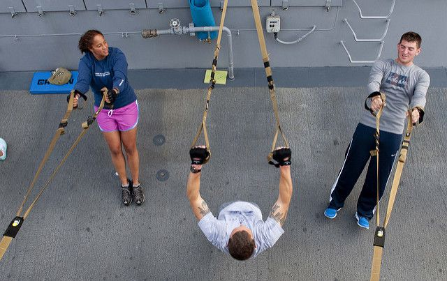 Two men and a woman working out with resistance bands.