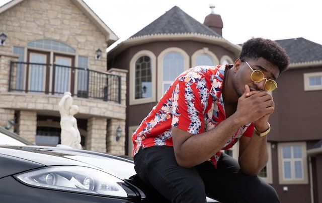 Man sits on hood of expensive car in front of a mansion.
